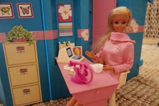 Barbie, attablée au bureau de son studio (portable !)